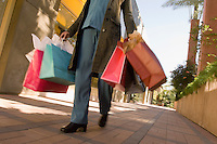 Woman carrying shopping bags low section
