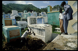 CAP HAITIEN, HAITI - Two boys watch as a grave digger covers their grandmother's coffin after she fell ill and died from lack of proper food and medical care. (PHOTO © JOCK FISTICK)....