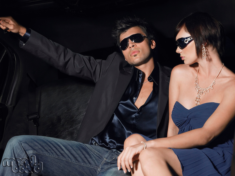 Couple in evening wear and sunglasses in back of limousine