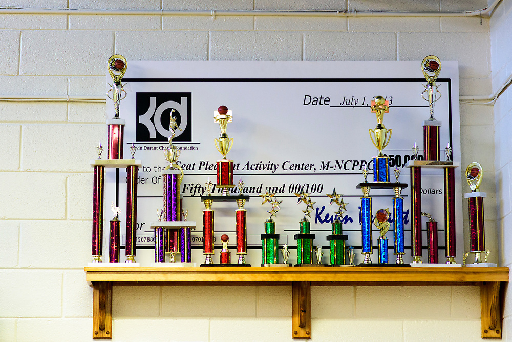 Capitol Heights, Maryland - March 29, 2017: An enlarged check for $50,000 signed by Kevin Durant sits behind trophies in Seat Pleasant Activity Center's Kevin Durant Den. NBA super star Kevin Durant has donated a substantial amount of money to help renovate the Seat Pleasant Activity Center where he learned to play basketball. Durant's AAU coach and mentor Charles &quot;Chuckie&quot; Craig, who worked at the Activity Center, was gunned down in May 2005 at the age of 35. Durant wears #35 in Craig's honor.<br /> <br /> <br /> NBA Superstar Kevin Durant's jersey number &quot;35&quot; is a tribute to his rec. league coach and mentor Charles &quot;Chuckie&quot; Craig, who was gunned down in at a night club in Laurel, Md., in 2005 when he was 35 years old. <br /> <br /> CREDIT: Matt Roth for The New York Times<br /> Assignment ID: 30204524A