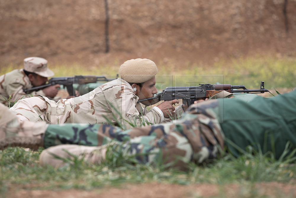 © Licensed to London News Pictures. 30/03/2015. Erbil, Iraq. Kurdish peshmerga fighters zero the sights on their Kalashnikov rifles as part of a training package run by coalition forces at a military training area near Erbil, Iraq.<br /> <br /> The training is part of a four week long package, the first to be held with a complete peshmerga battalion, run by coalition forces mobile training teams (MTT) in Kurdistan with the aim to make the peshmerga more efficient in combatting the Islamic State. Photo credit: Matt Cetti-Roberts/LNP