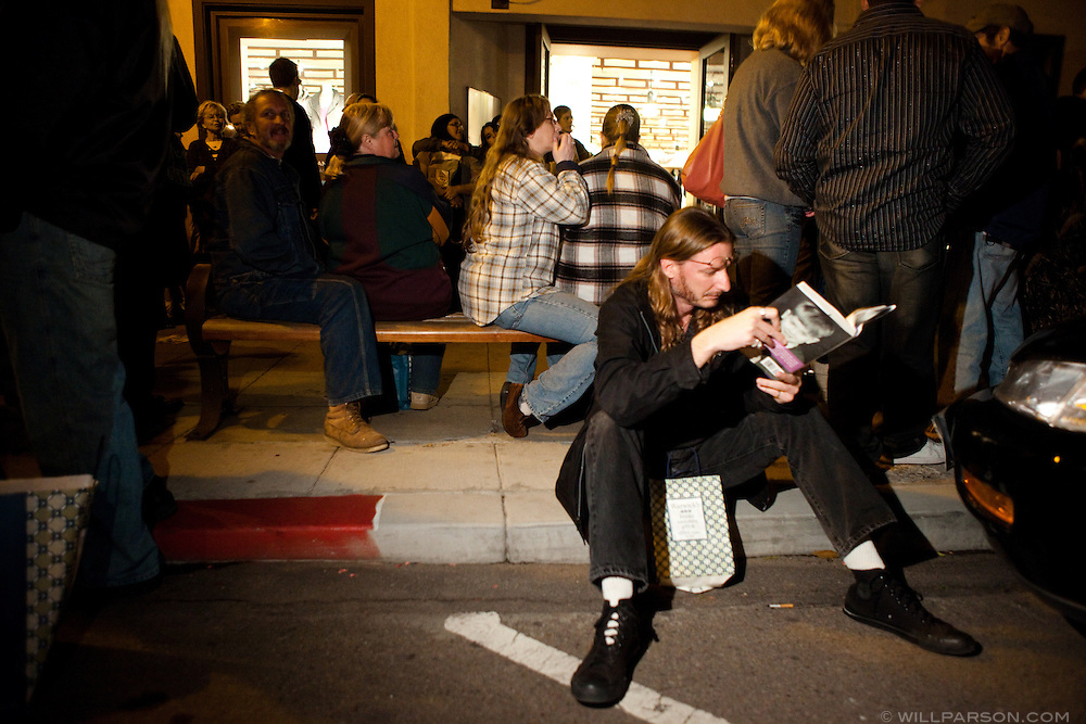 Matthew Dunn from Ocean Beach reads Ozzy Osbourne's book, I Am Ozzy, on the sidewalk on Girard Avenue while hundreds waited to get their books signed.