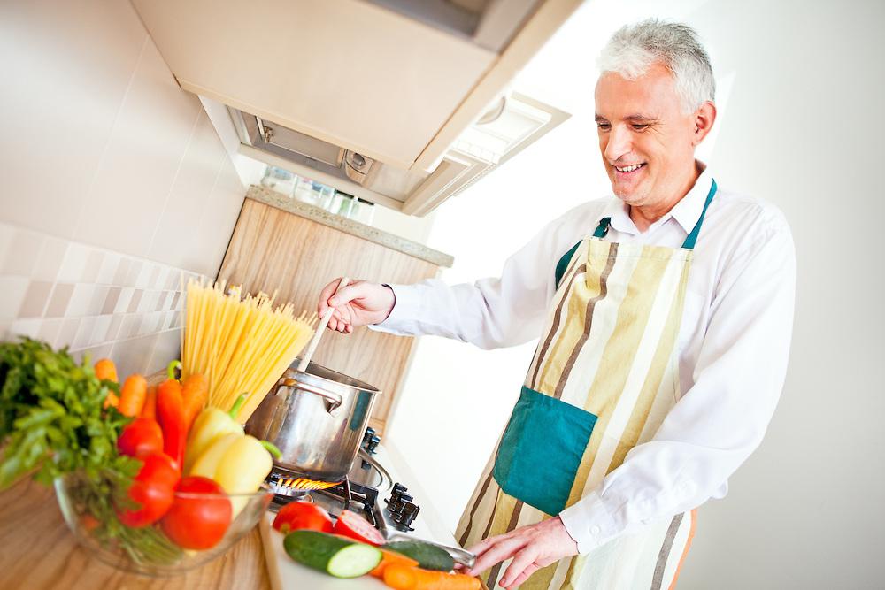 A handsome senior man cooking.