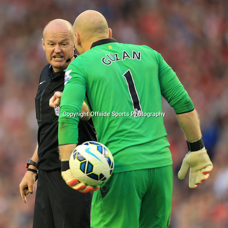 13th September 2014 - Barclays Premier League - Liverpool v Aston Villa - Referee Lee Mason points at the ball held by Villa goalkeeper Brad Guzan - Photo: Simon Stacpoole / Offside.