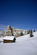 A snow covered wooden barn at the Alta Badia ski resort with Sassongher Mountain in the background.  Corvara, The Dolomites, South Tyrol, Italy