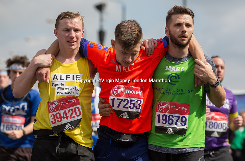 Alfie Millar and Marc Roby help Matt Carpanini pass through Blackfriars with a couple of miles still to go. The Virgin Money London Marathon, 23rd April 2017.<br /> <br /> Photo: Charlotte Wilson for Virgin Money London Marathon<br /> <br /> For further information: media@londonmarathonevents.co.uk