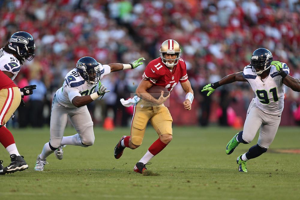 San Francisco 49ers quarterback Alex Smith (11) runs against Seattle Seahawks defensive tackle Jason Jones (90) on Thursday, Oct. 18, 2012 at Candlestick Park in San Francisco, CA. (AP Photo/Jed Jacobsohn)