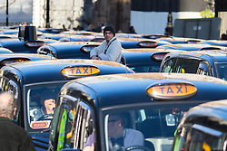 Whitehall, London, February 10th 2016. A cabbie watches proceedings as an estimated 8,000 cabbies hold a go-slow in protest against what they say is unfair competition from minicab and Uber drivers who do not have to undergo the rigorous training and checks required for the licenced taxi trade. ///FOR LICENCING CONTACT: paul@pauldaveycreative.co.uk TEL:+44 (0) 7966 016 296 or +44 (0) 20 8969 6875. ©2015 Paul R Davey. All rights reserved.