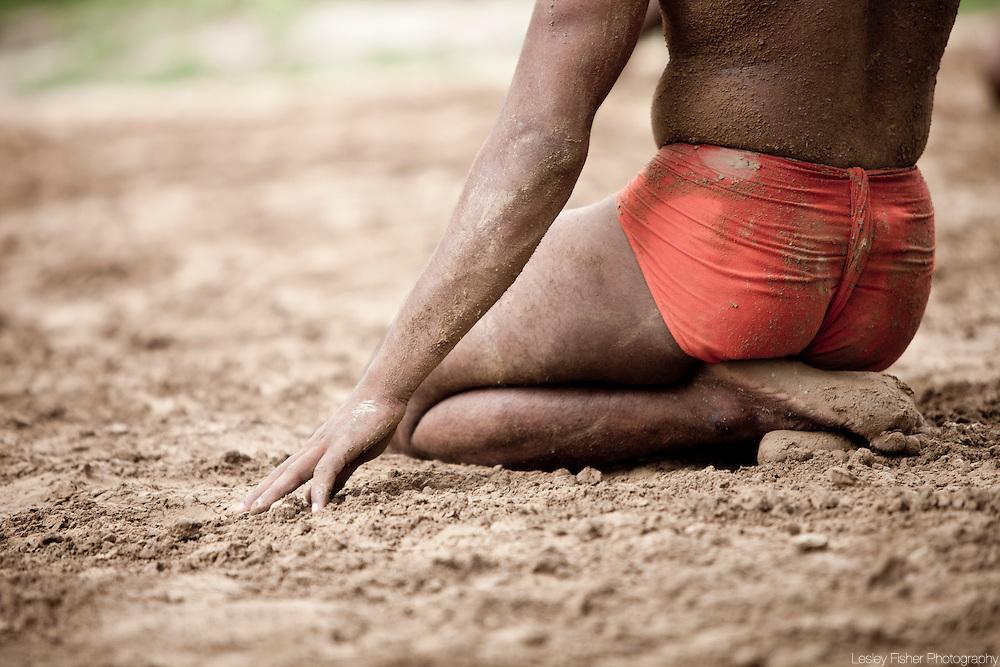 Kushti wrestler kneeling on the dirt waiting to practice the ancient sport, Varanasi, India