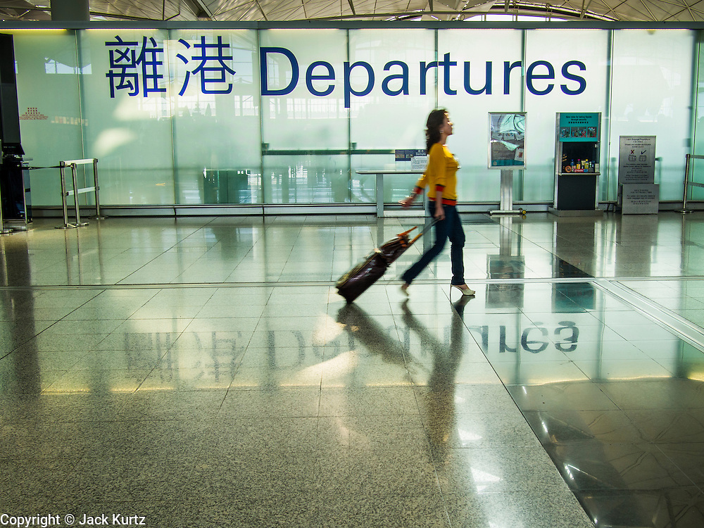 10 AUGUST 2013 - HONG KONG:   People walk past the departures area in Hong Kong International Airport. Hong Kong is one of the two Special Administrative Regions of the People's Republic of China, Macau is the other. It is situated on China's south coast and, enclosed by the Pearl River Delta and South China Sea, it is known for its skyline and deep natural harbour. Hong Kong is one of the most densely populated areas in the world, the  population is 93.6% ethnic Chinese and 6.4% from other groups. The Han Chinese majority originate mainly from the cities of Guangzhou and Taishan in the neighbouring Guangdong province.      PHOTO BY JACK KURTZ