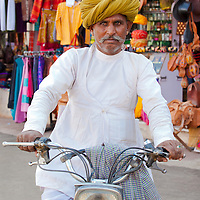 Man with beautifully wrapped turban poses with classic motorcycle in Pushkar, Rajasthan, India