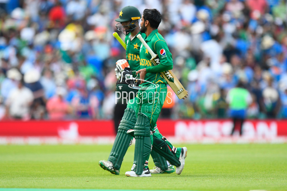 Imad Wasim of Pakistan and Mohammad Hafeez of Pakistan walk off the field after 50 overs having helped the team score 338 during the ICC Champions Trophy final match between Pakistan and India at the Oval, London, United Kingdom on 18 June 2017. Photo by Graham Hunt.