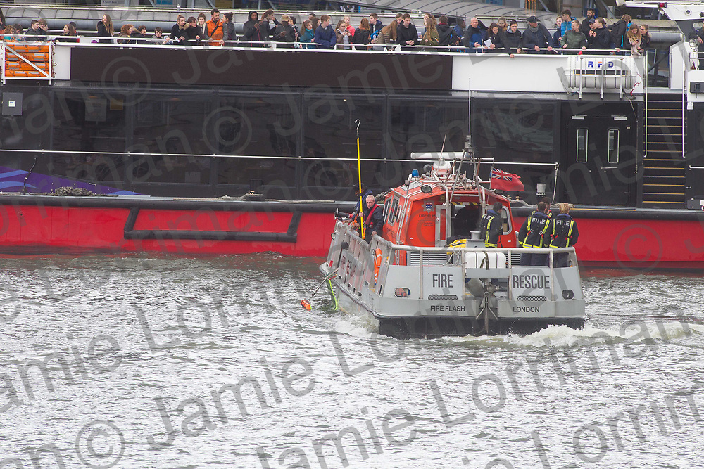 Terrorist incident on Westminster Bridge, London<br /> <br /> Pictured: A boat worker and fire crews retrieve an unknown object from the Thames under Westminster Bridge, London<br /> <br /> Jamie Lorriman<br /> mail@jamielorriman.co.uk<br /> www.jamielorriman.co.uk<br /> 07718 900288