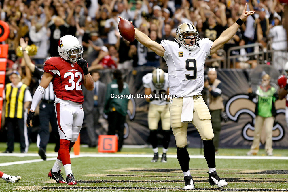 Sep 22, 2013; New Orleans, LA, USA; New Orleans Saints quarterback Drew Brees (9) celebrates a touchdown as Arizona Cardinals defensive back Tyrann Mathieu (32) looks on during the second half of a game at Mercedes-Benz Superdome. The Saints defeated the Cardinals 31-7. Mandatory Credit: Derick E. Hingle-USA TODAY Sports