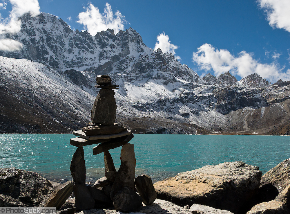 A tripod cairn of rocks at third Gokyo Lake (Dudh Pokhari, 15,584 feet / 4750 meters), in Sagarmatha National Park, Nepal, in the Himalaya mountain range of Asia. Sagarmatha National Park was created in 1976 and honored as a UNESCO World Heritage Site in 1979.