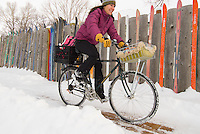 A young woman bike commutes through the snow in Jackson, Wyoming.