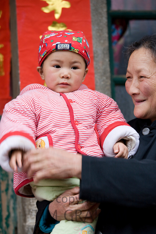 Woman carries granddaughter in Fuli, Xingping. China has a one child family planning policy to limit population.