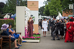 © Licensed to London News Pictures. 19/06/2018. London, UK.  Racegoers pose for photographs while attending day one of Royal Ascot at Ascot racecourse in Berkshire, on June 19, 2018. The 5 day showcase event, which is one of the highlights of the racing calendar, has been held at the famous Berkshire course since 1711 and tradition is a hallmark of the meeting. Top hats and tails remain compulsory in parts of the course. Photo credit: Ben Cawthra/LNP