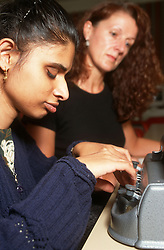 Young girl with visual impairment using Braille machine with teacher in background,