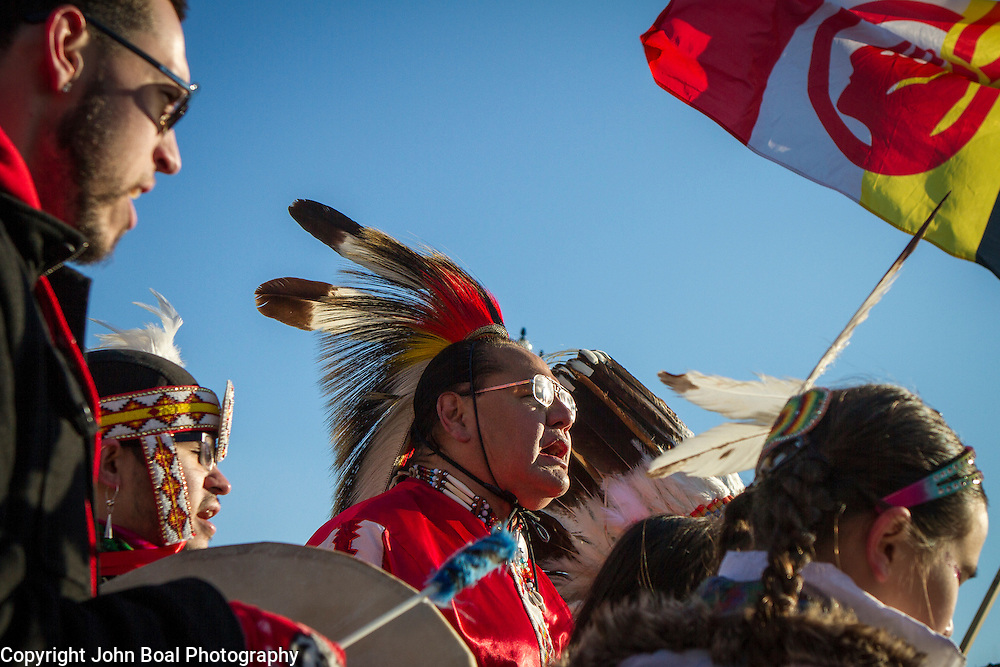 Beneath the American Indian Movement flag, Dennis Zotigh, Kiowa, center, sings and drums with family members during a protest and march from in front of the U.S. Capitol to the EPA, about the North Dakota Access Pipeline, as well as the effort to free Leonard Peltier.  Saturday, December 10, 2016. John Boal Photography