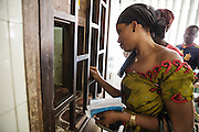 A woman waits to pick up her prescription from the pharmacy at the Koumassi General hospital in Abidjan, Cote d'Ivoire on Friday July 19, 2013.