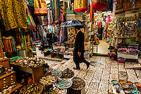 An orthodox Jew walking through the Arab bazaar (suq) in the old city of Jerusalem, Israel in the rain.