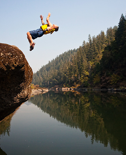 Young man wearing a life jacket does a backflip off a rocky ledge into a river. River rafting trip, Rogue River, Oregon, USA.