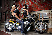 Brass Ball Bobber motorcycle in urban scene with two hot chicks after one rockabilly guy.  Model and product released.