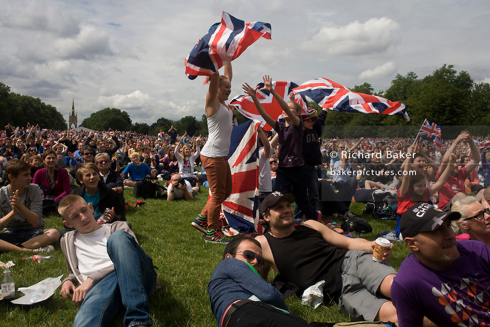 British spectators celebrate a gold medal win by Team GB Triathlete Alistair Brownlee in the Triathlon, held in Hyde Park during the London 2012 Olympics, the 30th Olympiad. Girl sports fans wave their union jack flags above their heads as thousands watch a giant TV screen with the Albert Memorial in the distance. Brownlee came first followed by Spain's Javier Gomez then Jonathan Brownlee (brother of the winner). The venue was the Hyde Park 142 hectares (350 acres) Hyde Park in the heart of the capital, one of the largest parks in central London and the site of the Victorian Great Exhibition of 1851.