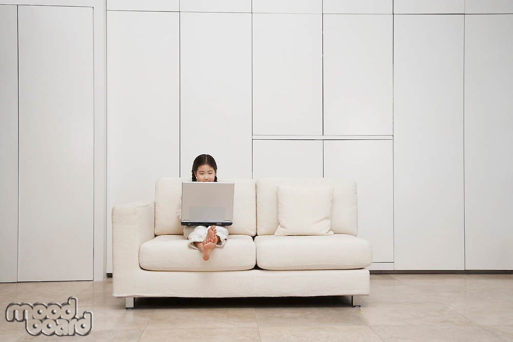 Young barefoot Girl Using Laptop on Sofa