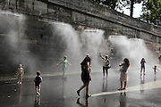 People enjoying the cooling water mister system of Paris Plage 2013 in a morning of a heatwave day, banks of the river Seine, Paris, France. Picture by Manuel Cohen