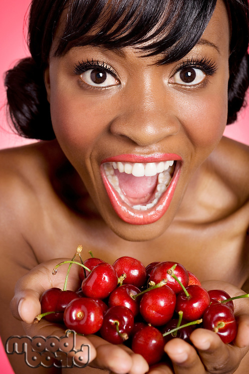 Portrait of woman with hands full of cherries