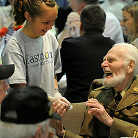 Fourth-grader Cassidy Faulkner shares a laugh with Army veteran Bill Miller after serving him a plate of food during a veterans celebration and luncheon at Eastmont Community School on Wednesday.