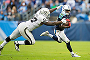 NASHVILLE, TN - NOVEMBER 29:  Kendall Wright #13 of the Tennessee Titans is tackled from behind by Mario Edwards Jr. #97 of the Oakland Raiders at Nissan Stadium on November 29, 2015 in Nashville, Tennessee.  The Raiders defeated the Titans 24-21.  (Photo by Wesley Hitt/Getty Images) *** Local Caption *** Kendall Wright; Mario Edwards Jr.