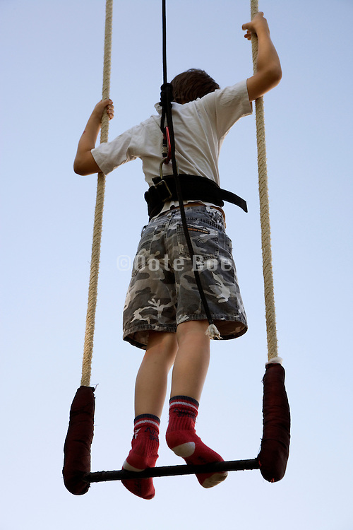young child standing on a trapeze