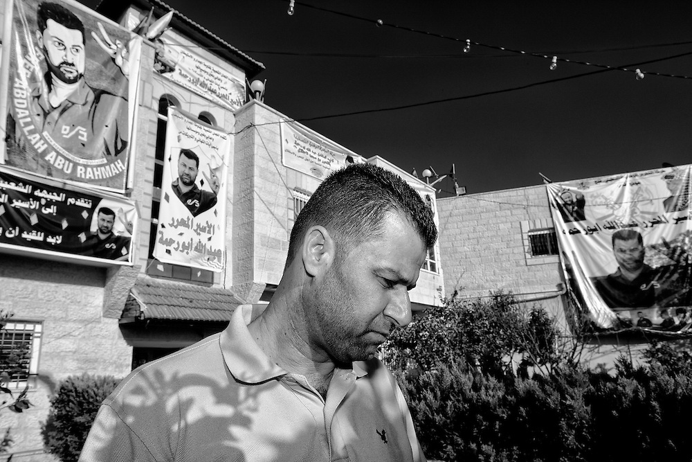 Abdullah Abdel Rahmah two days after his release from an Israeli prison, stands in front of banners that had been calling for his release. Bil'in. Mar. 18, 2011. West Bank, Palestine.