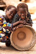 Children rest on a large wooden mortar in the village of Banankoro, Mali on Saturday August 28, 2010.