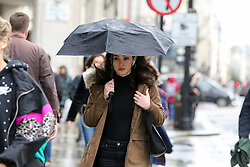 © Licensed to London News Pictures. 21/12/2019. London, UK. A Christmas shopper shelters from rain underneath an umbrella on London's Oxford Street. Retailers are expecting a rush of shoppers in the lead-up to Christmas. Photo credit: Dinendra Haria/LNP