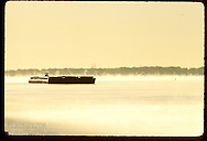 Barge moves upstream on Mississippi River as early-morn fog floats above water; near Elsah. Illinois