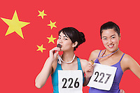 Portrait of young medalists standing against Chinese flag