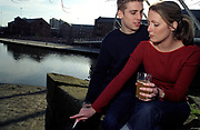 A couple sitting by a river, woman smoking a cigarette, UK 2000's