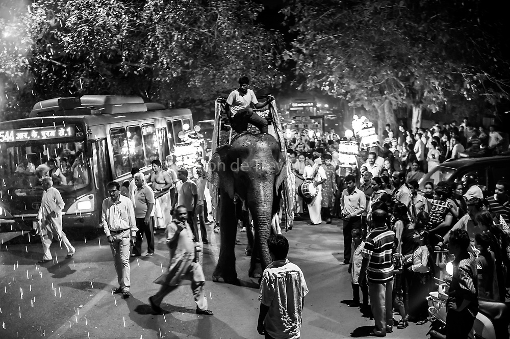 29th August 2014, Sarojini Nagar, New Delhi, India. Female elephant Gulabo ridden by her handler leads a  Sidhi Budhi Vinayaka procession through the streets as a firework goes off, near the Sree Vinayaka Mandir in New Delhi, India on the 29th August 2014 as part of the Ganesh Chaturthi religious festival<br /> <br /> Ganesh Chaturthi is the Hindu festival celebrated in honour of the god Ganesha, the elephant-headed, remover of obstacles and the god of beginnings and wisdom.<br /> <br /> Elephant handlers (Mahouts) eke out a living in makeshift camps on the banks of the Yamuna River in New Delhi. They survive on a small retainer paid by the elephant owners and by giving rides to passers by. The owners keep all the money from hiring the animals out for religious festivals, events and weddings, they also are involved in the illegal trade of captive elephants. The living conditions and treatment of elephants kept in cities in North India is extremely harsh, the handlers use the banned 'ankush' or bullhook to control the animals through daily beatings, the animals have no proper shelters are forced to walk on burning hot tarmac and stand for hours with their feet chained together. <br /> <br /> PHOTOGRAPH BY AND COPYRIGHT OF SIMON DE TREY-WHITE + 91 98103 99809<br /> email: simon@simondetreywhite.com<br /> Photographer in Delhi