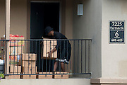 A man carries foot into the apartment where Thomas E. Duncan, the first confirmed Ebola virus patient, was staying with family in Dallas, Texas on October 2, 2014. Duncan is now being treated at Texas Health Presbyterian Hospital Dallas. (Cooper Neill for The New York Times)