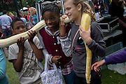 Local children enjoy handling a Burmese Python in their local park during a community festival.