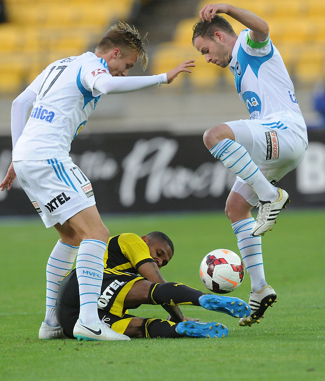 Melbourne Victory's James Jeggo, left and Leigh Broxham attempt to clear the ball from Phoenix's Kenny Cunningham in the A-League football match at Westpac Stadium, Wellington, New Zealand, Saturday, Januray 18, 2014. Credit:SNPA / Ross Setford