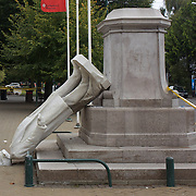 A fallen statue in Christchurch after a Powerful earth quake ripped through Christchurch, New Zealand on Tuesday lunch time killing at least 65 people as it brought down buildings, buckled roads and damaged houses, churches and the Cities Cathedral. 23rd February 2011.  Photo Tim Clayton