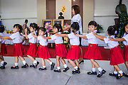 26 NOVEMBER 2012 - BANGKOK, THAILAND:   School children march past portraits of the King and Queen of Thailand on the way to paying their respects to the monarchy at Siriraj Hospital in Bangkok. Siriraj was the first hospital in Thailand and was founded by King Chulalongkorn in 1888. It is named after the king's 18-month old son, Prince Siriraj Kakuttaphan, who had died from dysentery a year before the opening of the hospital. It's reported to one of the best hospitals in Thailand and has been home to Bhumibol Adulyadej, the King of Thailand, since 2009, when he was hospitalized to treat several ailments. Since his hospitalization tens of thousands of people have come to pay respects and offer get well wishes. The King's 85th birthday is on Dec 5 and crowds at the hospital are growing as his birthday approaches. The King is much revered throughout Thailand and is seen as unifying force in the politically fractured country.      PHOTO BY JACK KURTZ