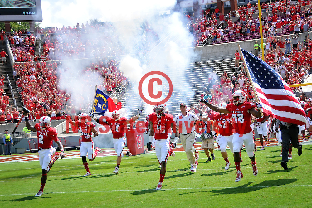 Fireworks shoot off as football coach Dave Doeren and team run out onto the field at Carter Finley Stadium.