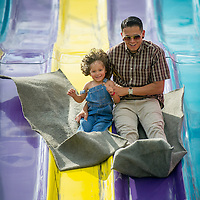 Luis Montoya slides with his son, Lucas, 3, on the opening day of the San Bernardino County Fair in Victorville, Saturday, May 24, 2014.  (Eric Reed/For The Sun)