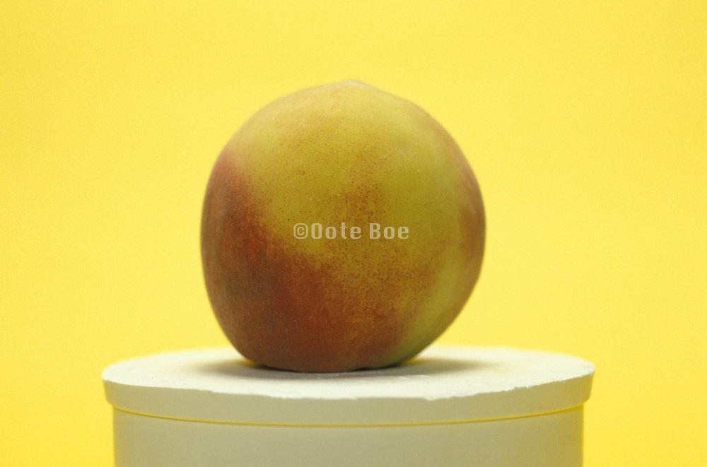 A whole peach on a pedestal